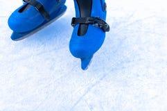Jambes d'un patineur de glace dans de vieux patins de cru Fond skratched par glace image stock