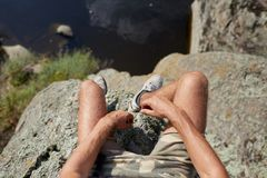Jambes d'un voyageur s'asseyant sur un dessus de montagne dehors Selfie des jambes sur un fond naturel brouillé Image stock