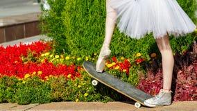 Jambes d'une ballerine sur une planche à roulettes Images libres de droits