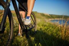 Jambes d'une femme dans des espadrilles avec une fin de bicyclette  Photo libre de droits