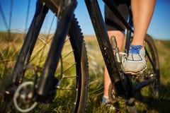 Jambes d'une femme dans des espadrilles avec une fin de bicyclette  Image libre de droits
