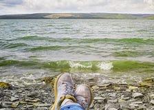 Jambes d'une femme dans des espadrilles détendant sur la plage rocheuse Photographie stock libre de droits