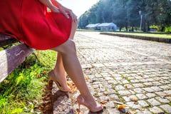 Jambes d'une femme s'asseyant sur un banc de parc Image stock