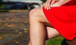 Jambes d'une femme s'asseyant sur un banc de parc Photos libres de droits