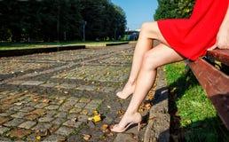 Jambes d'une femme s'asseyant sur un banc de parc Photos stock