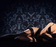Jambes d'une femme sexy et belle dans les sous-vêtements Photographie stock libre de droits