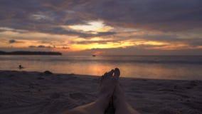 Jambes d'une femme sur une plage observant un coucher du soleil fantastique banque de vidéos
