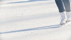 Jambes d'une fille de l'adolescence patinant habilement sur la patinoire publique extérieure, au ralenti banque de vidéos
