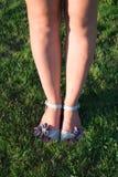 Jambes d'une fille en sandales Photographie stock libre de droits