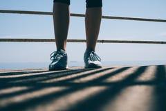 Jambes d'une jeune femme sportive dans des espadrilles bleues contre le dos Images stock