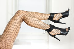 Jambes dans des bas de filet et des talons hauts à la mode Photos stock