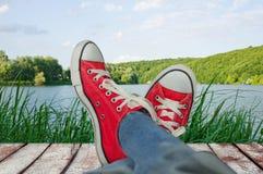 Jambes dans des chaussures de sport en vacances, avec vue sur la nature Image stock