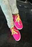 Jambes dans des chaussures en caoutchouc roses lumineux Images libres de droits