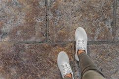 Jambes dans des espadrilles blanches sur les tuiles de rue Photos libres de droits
