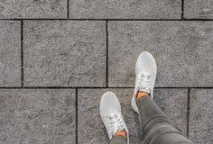 Jambes dans des espadrilles blanches sur les tuiles de rue Images libres de droits