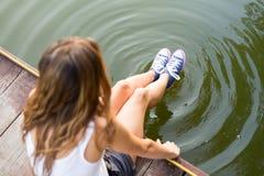 Jambes dans des espadrilles faisant des cercles dans une eau Photographie stock libre de droits