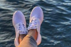 Jambes dans des espadrilles dans la perspective de la mer de soirée Photographie stock