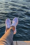 Jambes dans des espadrilles dans la perspective de la mer de soirée Images stock