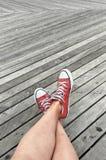 Jambes dans des espadrilles sur le fond en bois Photo libre de droits