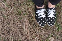 Jambes dans des espadrilles sur une herbe sèche Image stock