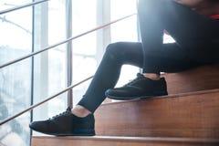 Jambes dans des guêtres noires de jeune sportive se reposant sur des escaliers Photos libres de droits
