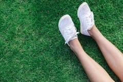 Jambes dans la jupe et blanc glissement-ONS dans l'herbe avec le copyspace Image stock