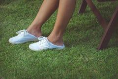 Jambes dans la jupe et blanc glissement-ONS dans l'herbe avec le copyspace Photographie stock libre de droits