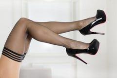 Jambes dans les bas et des chaussures de talons hauts Images stock