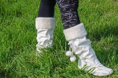 Jambes dans les bas noirs et bottes blanches sur l'herbe verte Photographie stock