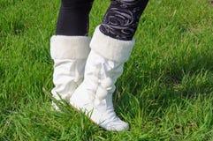 Jambes dans les bas noirs et bottes blanches sur l'herbe verte Image libre de droits