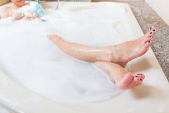 Jambes de averse et de lavage de belle fille dans la baignoire images stock