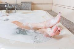 Jambes de averse et de lavage de belle fille dans la baignoire photos stock