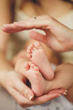 Jambes de bébé. Jambes nouveau-nées dans la main de parents. Pieds infantiles. Photographie stock