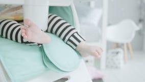 Jambes de bébé se reposant sur la chaise des hauts enfants banque de vidéos