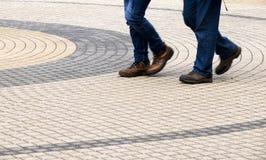 Jambes de deux hommes marchant sur le trottoir de cercles concentriques Images libres de droits