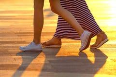 Jambes de deux personnes marchant sur le fond de la lumi?re du soleil photos stock