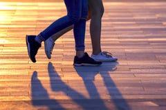 Jambes de deux personnes marchant sur le fond de la lumi?re du soleil photo stock