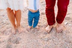 Jambes de famille sur la plage Parents avec des enfants sur la plage Fa Photographie stock