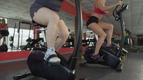 Jambes de femelle obèse pédalant lentement au vélo d'exercice dans le centre de fitness banque de vidéos