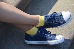 Jambes de femme avec les espadrilles bleues et les chaussettes jaunes Photos libres de droits