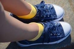 Jambes de femme avec les espadrilles bleues et les chaussettes jaunes Photo stock