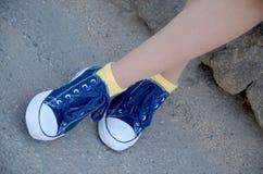 Jambes de femme avec les espadrilles bleues et les chaussettes jaunes Images libres de droits