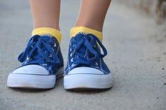 Jambes de femme avec les espadrilles bleues et les chaussettes jaunes Photographie stock libre de droits