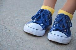Jambes de femme avec les espadrilles bleues et les chaussettes jaunes Image stock