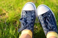 Jambes de femme avec les espadrilles bleues et les chaussettes jaunes Photos stock