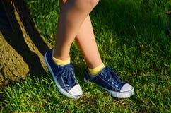 Jambes de femme avec les espadrilles bleues et chaussettes jaunes sur une herbe verte Photo stock