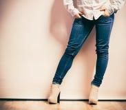 Jambes de femme dans des chaussures de talons hauts de pantalons de denim Image libre de droits