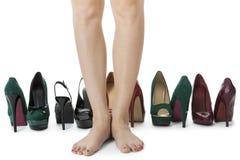 Jambes de femme dans des chaussures rouges entre d'autres talons hauts Image stock