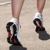 Jambes de femme dans des espadrilles sur l'asphalte Image libre de droits