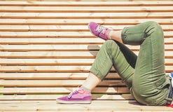 Jambes de femme dans le pantalon vert et l'espadrille pourpre se trouvant sur le Ben Images stock